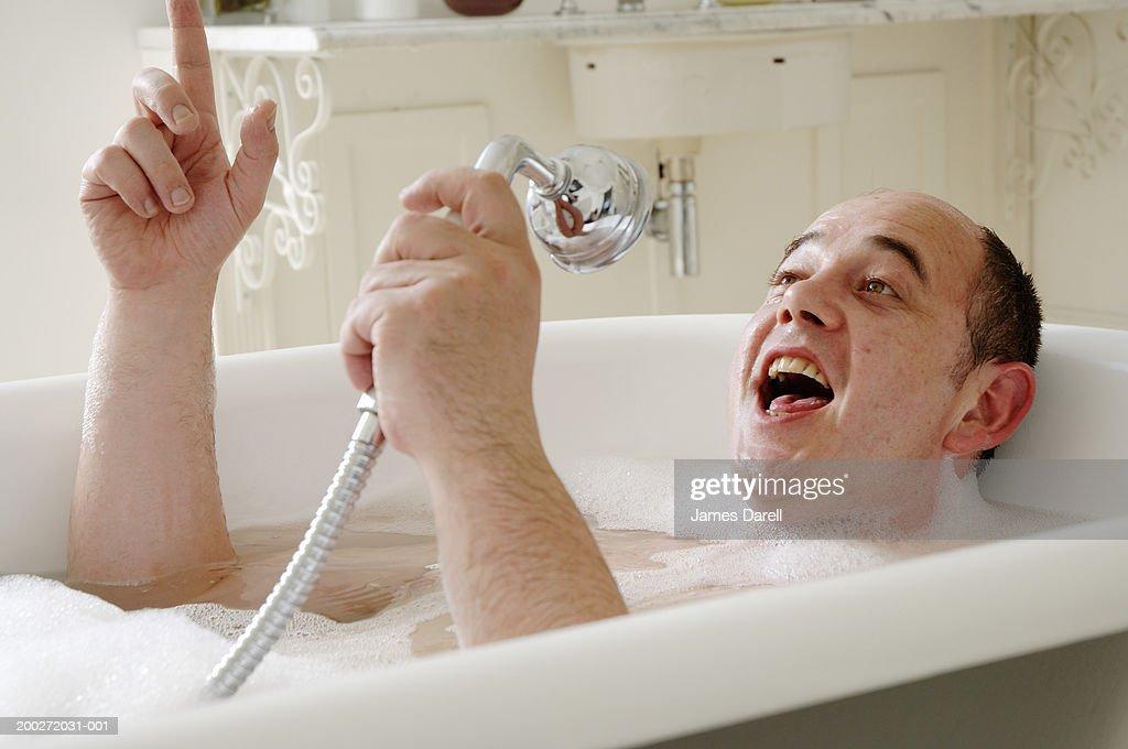 Man lying in bath singing into shower head, close-up