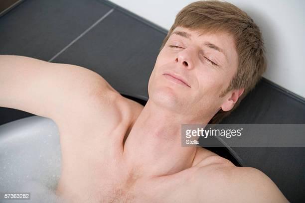 Man lying in bathtub with eyes closed