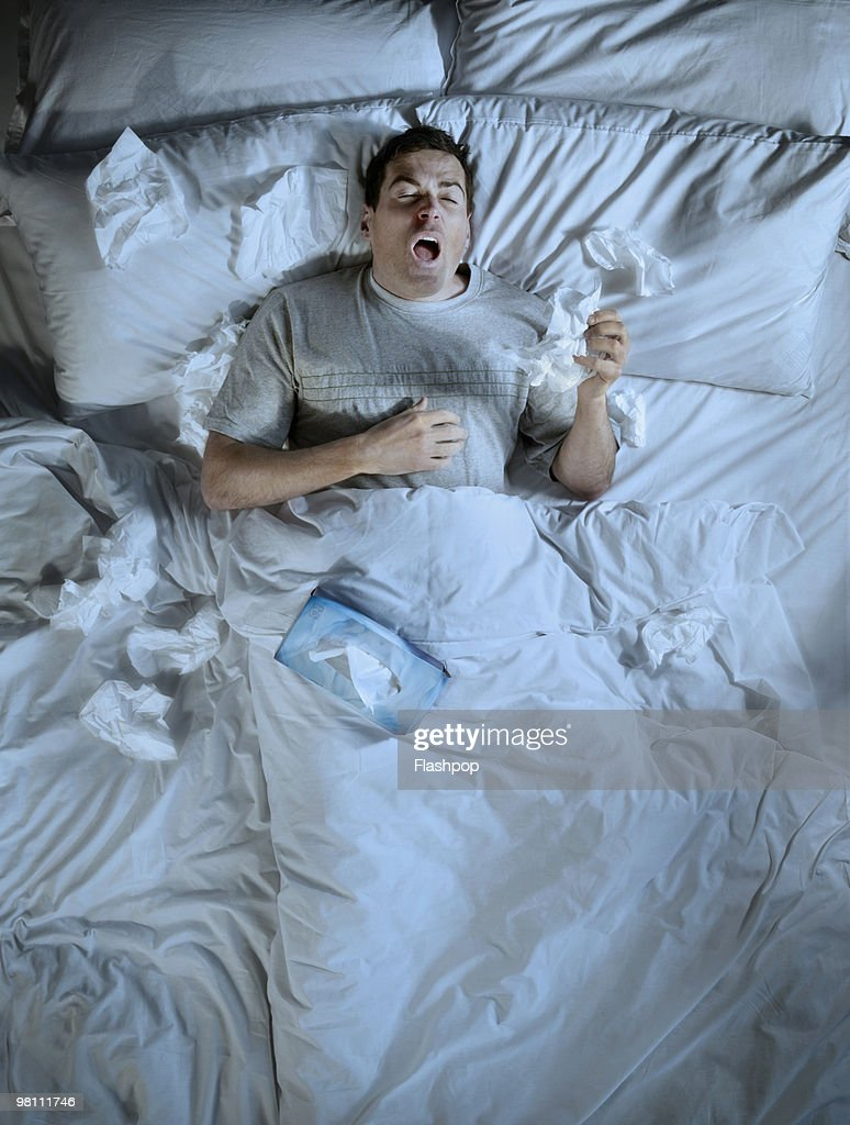 Man lying in bed sneezing into a tissue