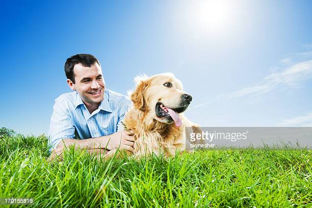 Man lying in park with his dog