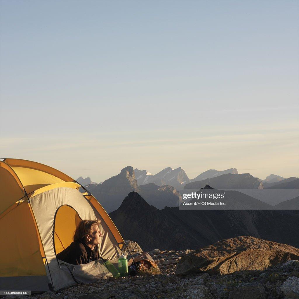 Man lying in tent opening on mountain ridge, sunrise : Stock Photo