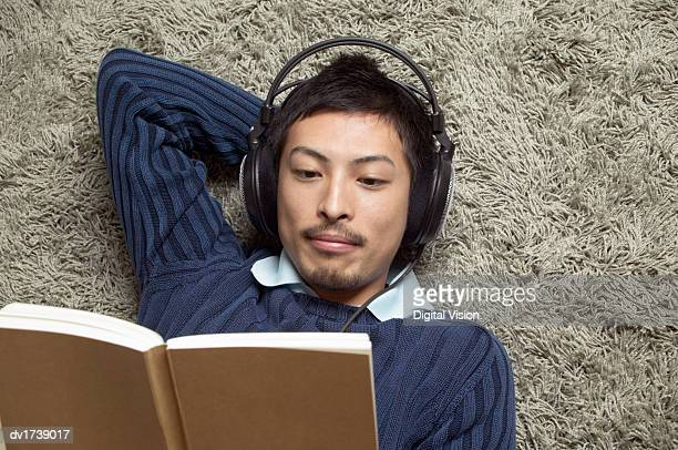 Man Lying Listening to Music and Reading a Book