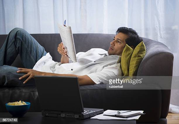 Man lying on a couch and reading a magazine