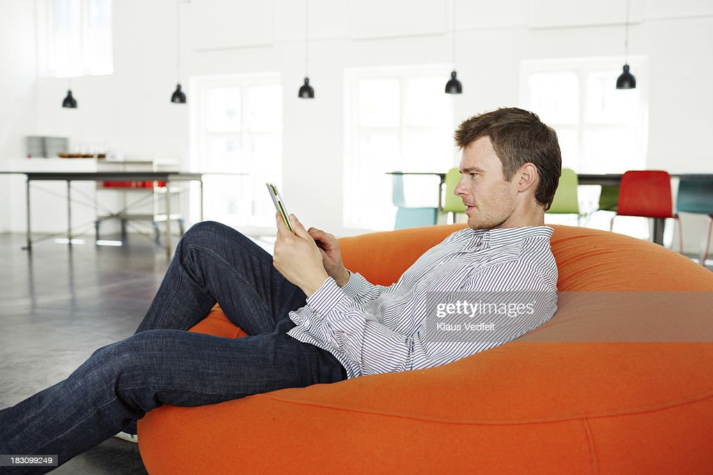 man lying on beanbag with tablet : Stock Photo