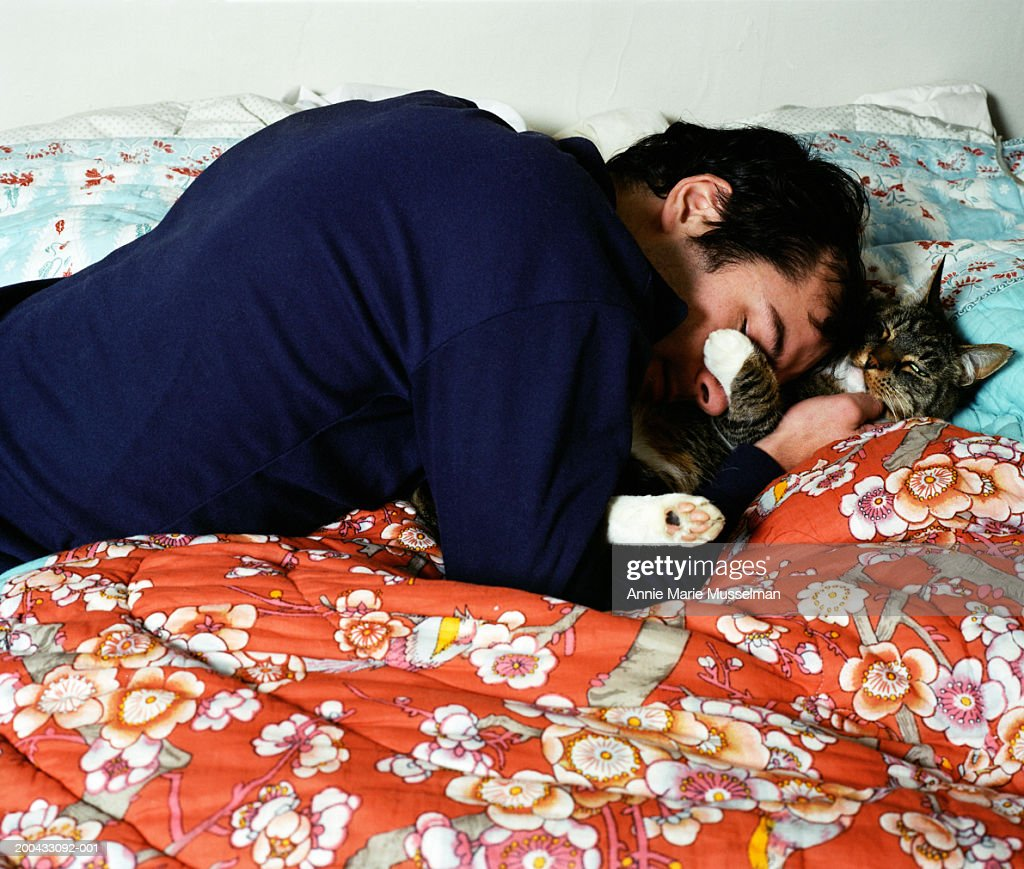 Man lying on bed, hugging cat, side view : Stock Photo