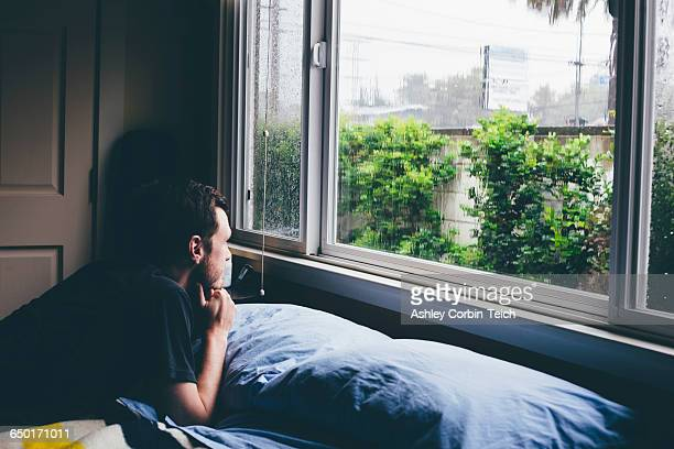 Man lying on bed staring through window at rain