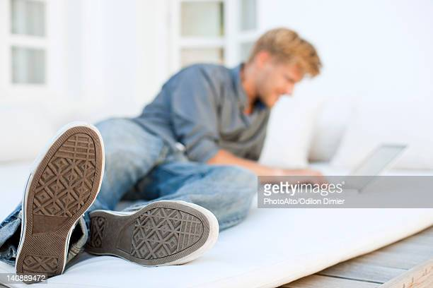 Man lying on bed using laptop computer