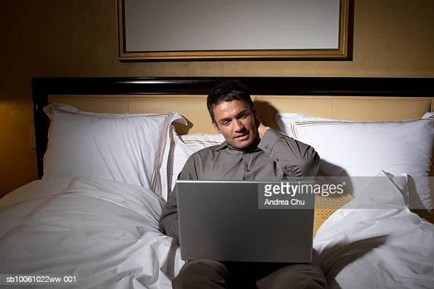 Man lying on bed, using laptop