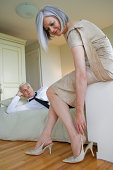 Man lying on bed, woman wearing shoes