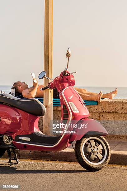 Man lying on boulevard ledge with book