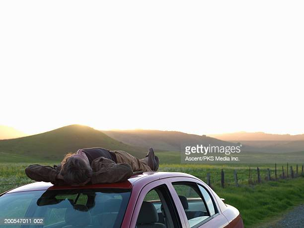 Man lying on car roof, hands behind head