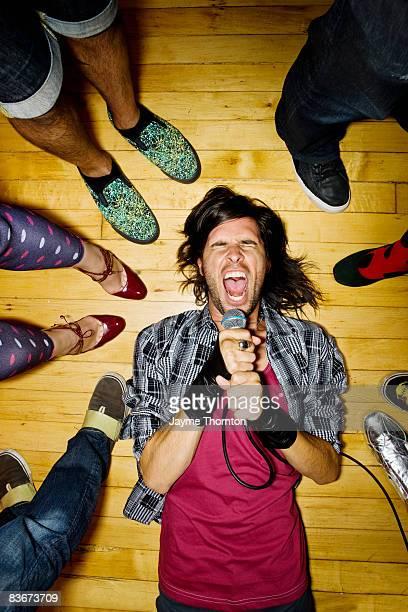 Man lying on club floor singing into microphone