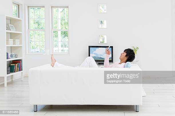 Man Lying On Couch Holding Cell Phone