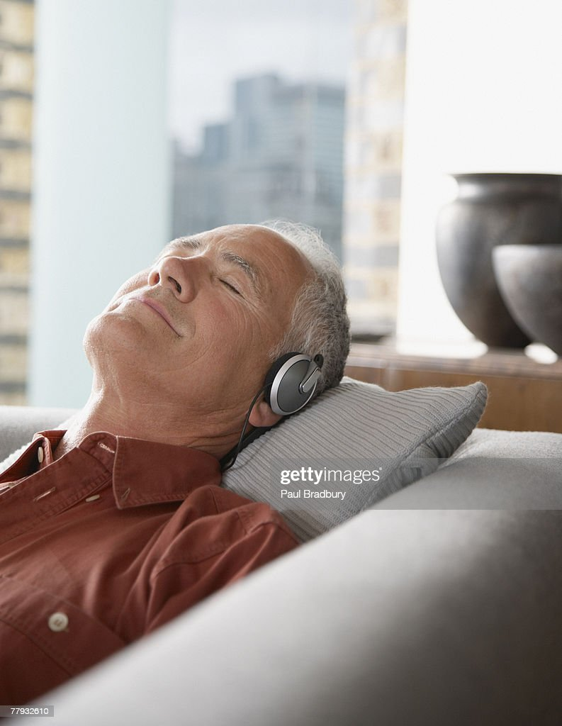 Man lying on couch wearing headphones : Stock Photo