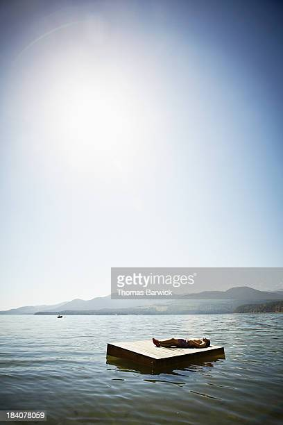 Man lying on floating dock mountains in background
