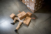Man lying on floor covered by cardboard boxes in warehouse