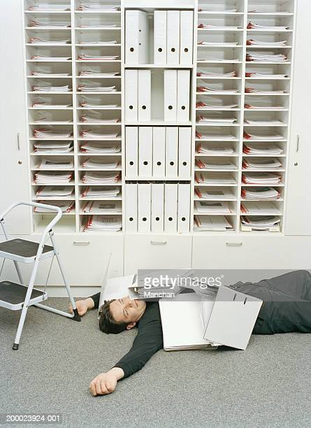 Man lying on floor covered in files by pigeonholes