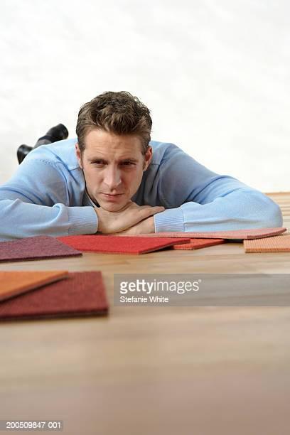 Man lying on floor looking at carpet samples
