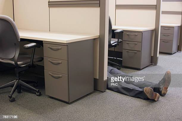 Man lying on floor of office cubicle