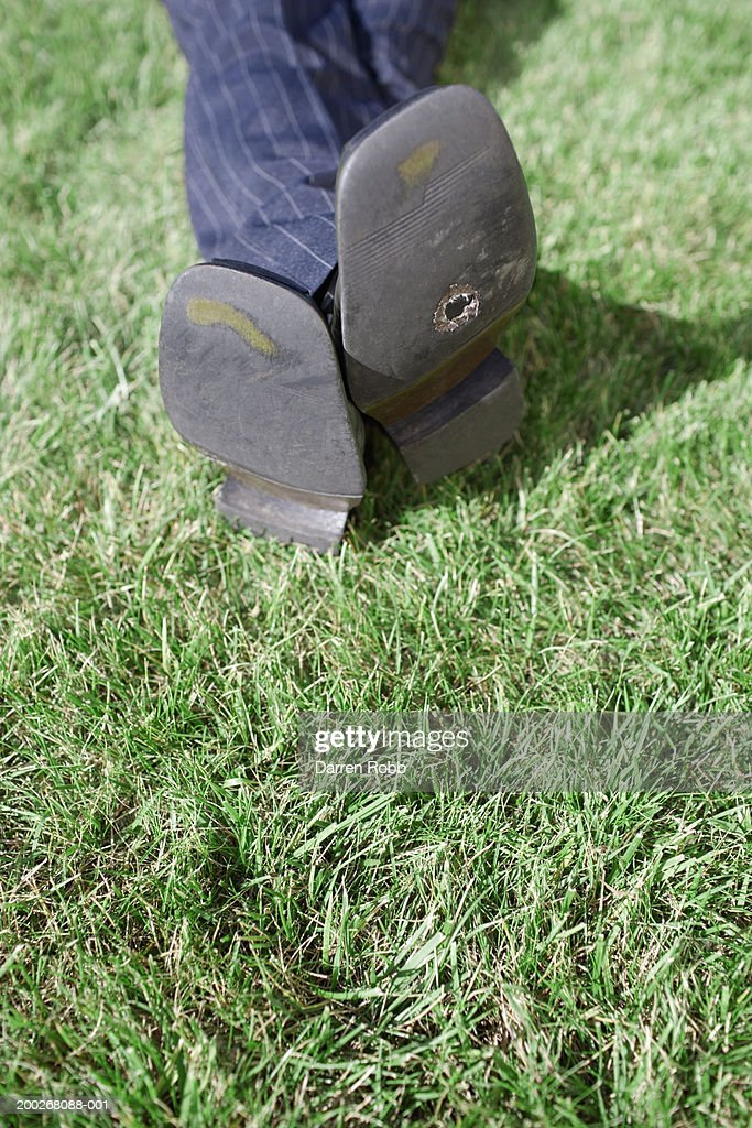 Man lying on grass, holes in his shoes, low section