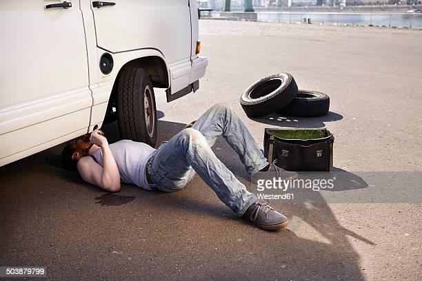 Man lying on ground repairing car
