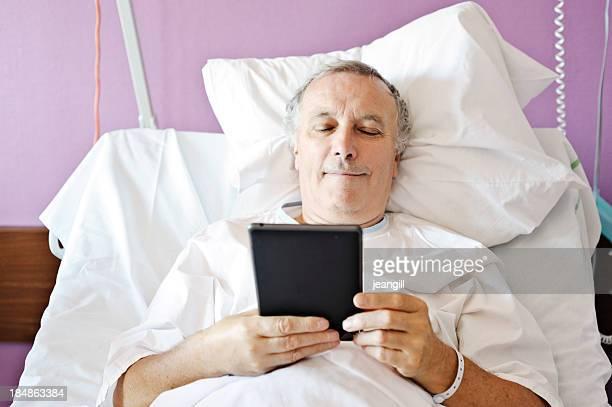 Man lying on hospital bed using digital tablet