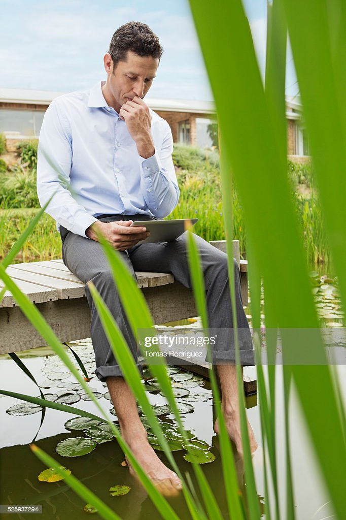 Man lying on jetty and using digital tablet : Stock Photo