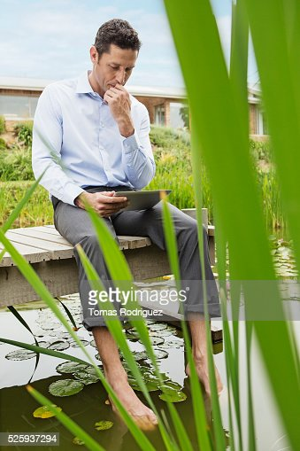 Man lying on jetty and using digital tablet : Photo