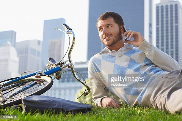 Man lying on lawn in park, talking on mobile phone