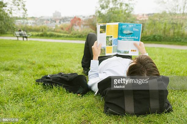 Man lying on lawn reading a magazine