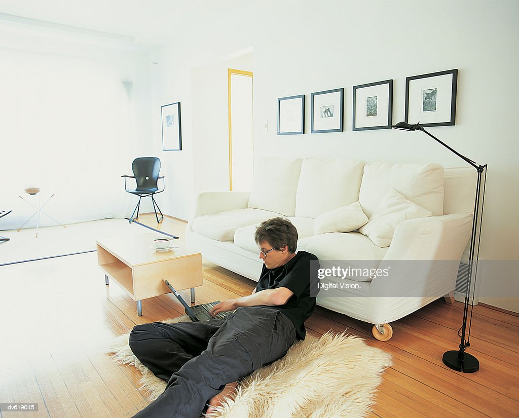 Man Lying on Living Room Floor, Using Laptop : Stock Photo