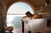 Man lying on massage table by the ocean