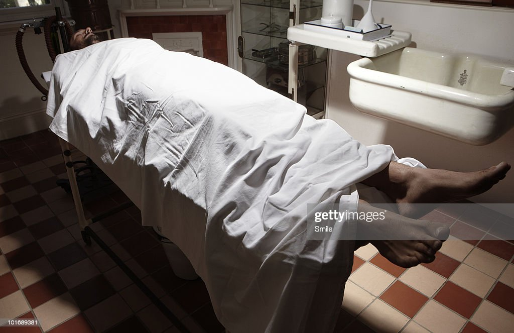 Man lying on operating table in antiquated theatre : Stock Photo