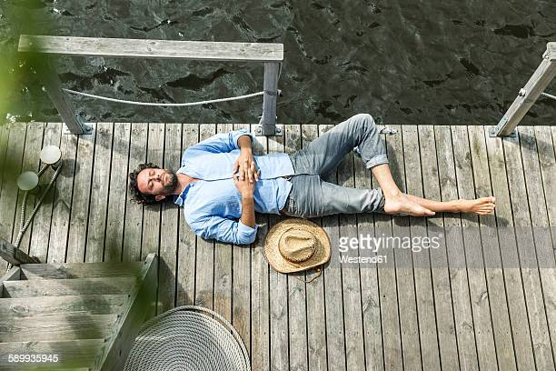 Man lying on platform at the waterside
