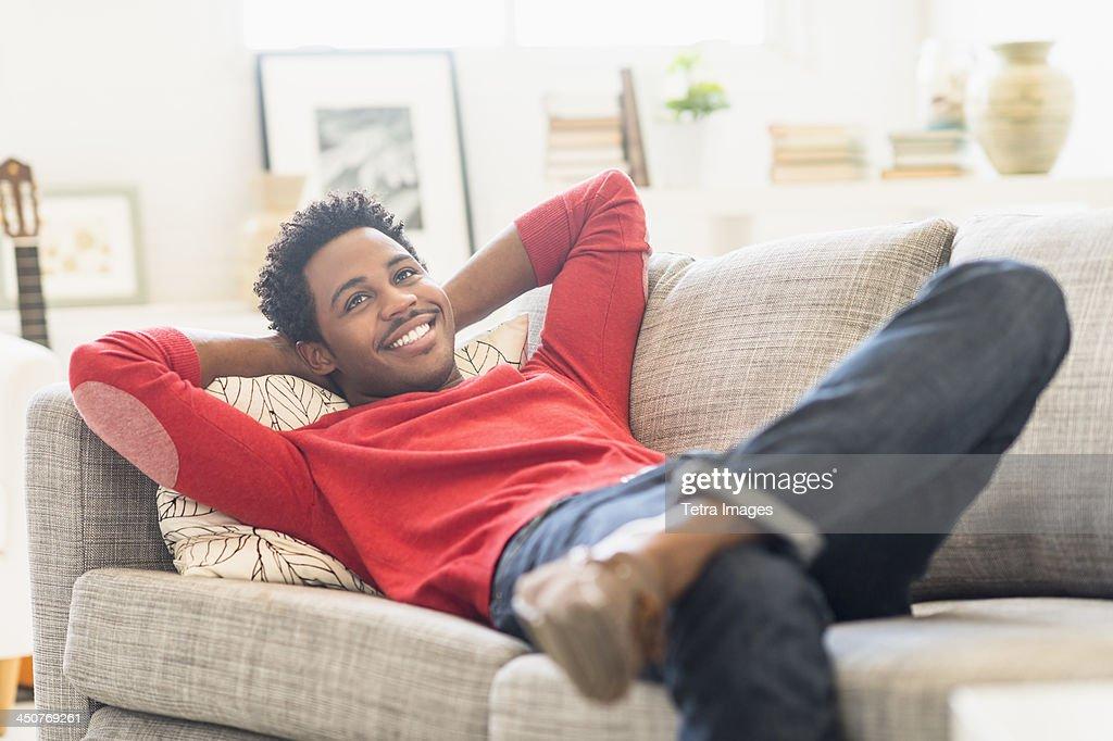 Man lying on sofa and smiling : Stock Photo