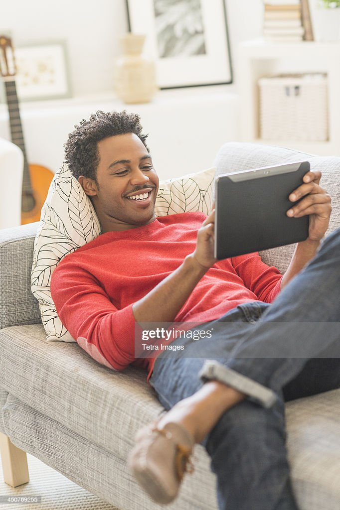 Man lying on sofa and using tablet PC : Stock Photo