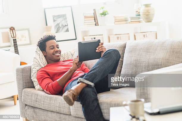 Man lying on sofa and using tablet PC