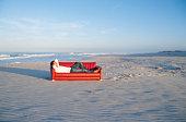 Man lying on sofa at beach