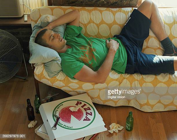 Man lying on sofa, discarded take-away boxes and beer bottles on floor