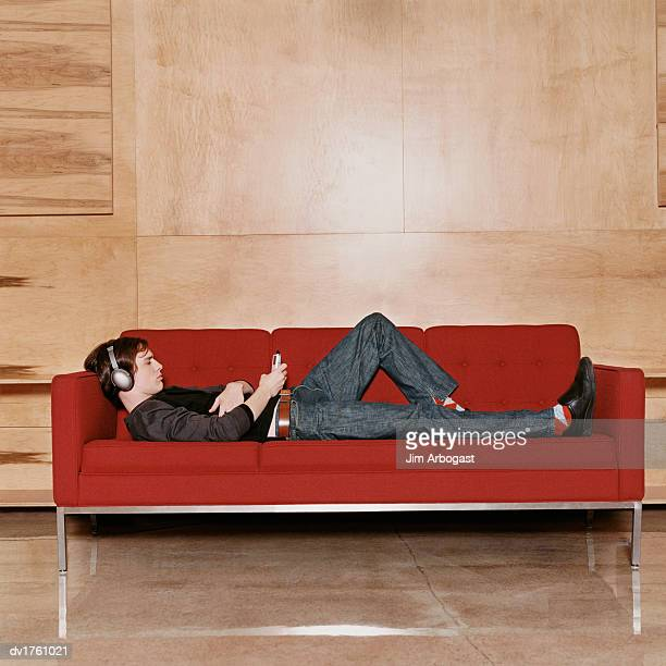 Man Lying on Sofa Listening to Headphones and Looking at His MP3 Player