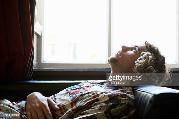 man lying on sofa relaxing