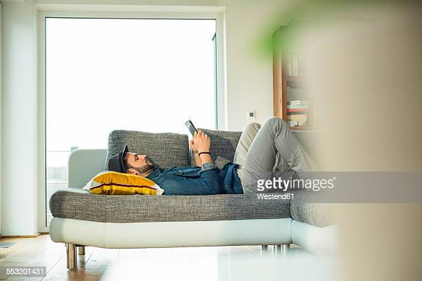 Man lying on sofa using digital tablet
