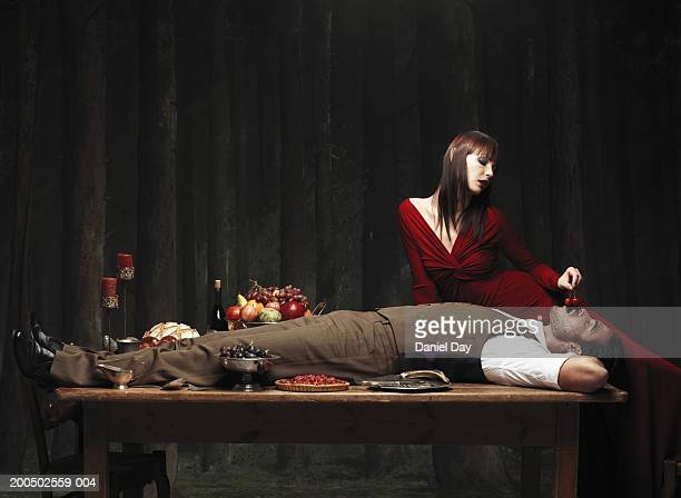 Man lying on table, woman feeding him cherries, side view