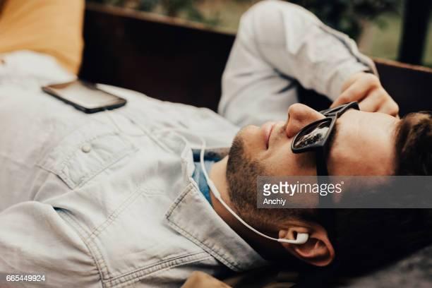 Mann auf der Bank liegend genießt die Musik, die, der er zu hören ist