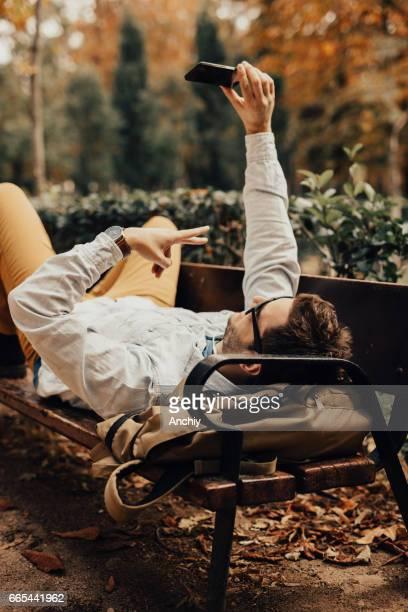 Mann auf der Bank liegend nimmt ein Selbstporträt