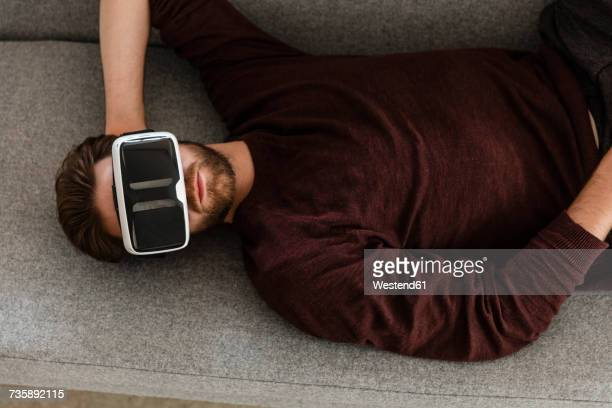 Man lying on the couch using Virtual Reality Glasses