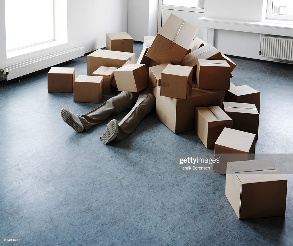 Man lying on the floor covered with boxes. : Stock Photo