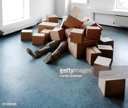 Man lying on the floor covered with boxes.