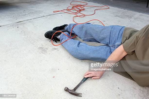 Man lying on the floor with a hammer in his hand