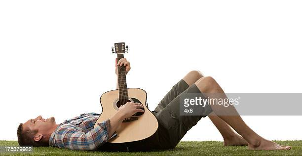 Man lying on the grass and playing a guitar